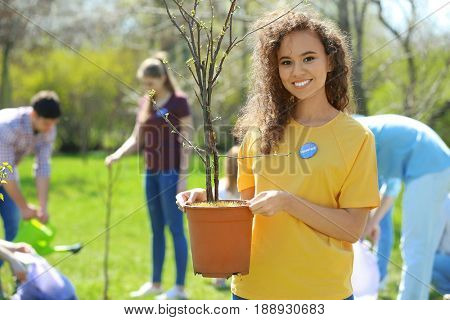 Beautiful African American volunteer with team outdoors