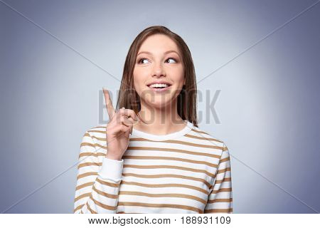 Beautiful quick-witted young woman on gray background