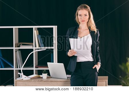 Confident Young Businesswoman With Hand In Pocket Holding Paper And Looking At Camera