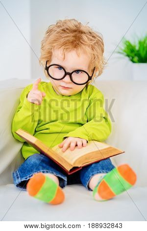 Small three year old boy in glasses is reading fairy tales. Educational concept.