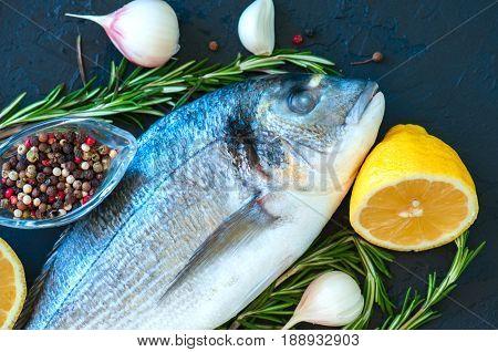 Close Up Of Fresh Raw Dorado Fish, Rosemary Herb Garlic Pepper And Half Of Lemon On A Black Slate Ba