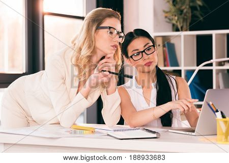 Young Multiethnic Businesswomen In Formalwear Looking At Laptop At Office