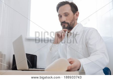 Peer review. Distinguished handsome plastic surgeon making a research on his computer while preparing an implant for demonstrating his explanation