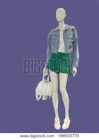 Full-length female mannequin dressed in blue jeans jacket and green shorts. Isolated. No brand names or copyright objects.