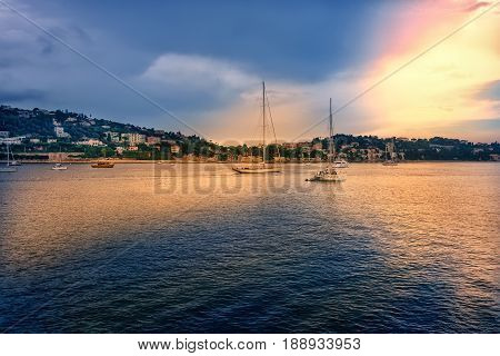Harbor in Nice France with anchored sailboats and a warm glow sky.