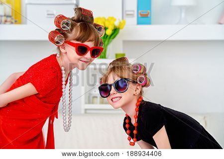 Two funny little girls with curlers in their hair are going to children's party. Kid's fashion. Family at home.