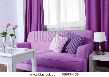 Lilac color accent in modern interior. Comfortable couch and table with flowers in living room