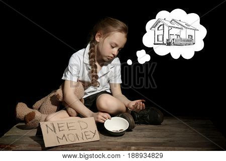 Little girl dreaming about home while panhandling on black background. Poverty concept