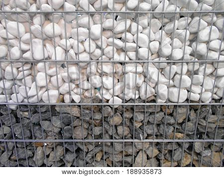 Two types of stone, gravel and granite, in a wire cage structure for the construction of retaining walls. Suitable for topics of road construction or traffic safety, but also as the background