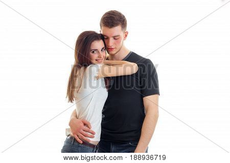 cute young brunette snuggled to the guy and he's hugging isolated on a white background close-up