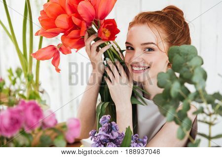 Young redhead woman florist looking up at camera and holding red tulips in workshop