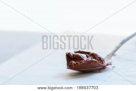 Melted Chocolate Paste In A Spoon On A Whte Stone Background. Close Up And Copy Space.