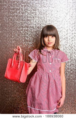 small pretty girl or cute fashionable child with long brunette hair and adorable smiling happy face in checkered dress with female red leather bag on metallic silver background