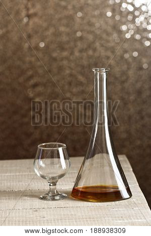 Bottle With Whiskey Inside, Next To Empty Glass