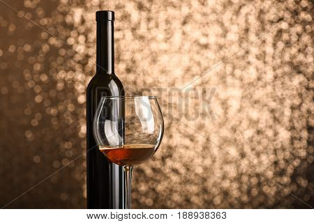 Alcohol beverage in glass near wine bottle on sparkling metallic background with copy space