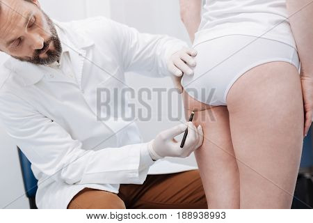Improving proportions. Careful precise wonderful doctor using special marker for putting guidelines on patients body while preparing for plastic surgery