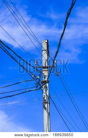 High voltage electric pole against blue sky and clouds and bright sun. High voltage electric pole.
