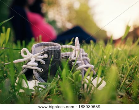 Close up view of little children shoes in grass and blurred silhouette of pregnant woman on background. Shallow DOF, focus on foreground. Pregnancy concept. Copy space.