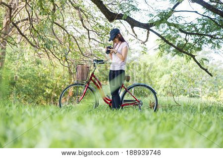 Women And Bike With Camera Take Photo Of The Nature City Park