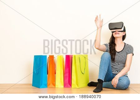 Woman Sitting On Wooden Floor With Shopping Bags