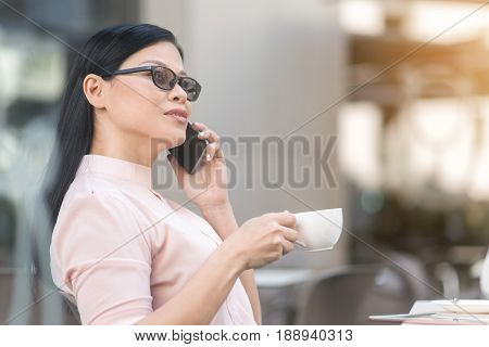 Serious asian businesswoman speaking by mobile while tasting cup of coffee in confectionary shop