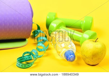 Concept Of Healthy Lifestyle With Purple Yoga Mat And Dumbbells