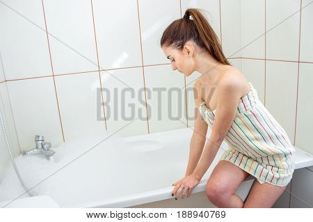 a young girl with a ponytail and a towel on the body sits on the bathtub and tries to hand water close-up