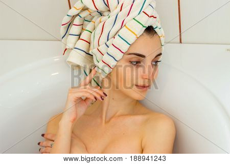 beautiful gentle girl with towel on the hair lies in the bathroom removing head close-up