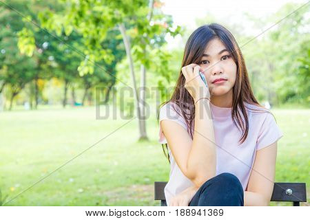 Woman Sitting On Bench Using Smartphone In The Citypark.