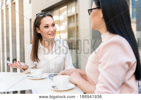 Cheerful female making communication with coworker while gesturing hands. They sitting in cafe