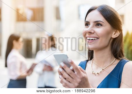Lady expressing happiness while noting sms by mobile outdoor. She looking away