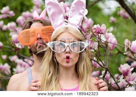 woman or cute girl and handsome man or macho making fish face lips grimace in funny glasses and rosy bunny ears on blossoming floral environment. Couple in love. Spring. Easter celebration