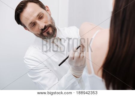 Petite client. Handsome trained dedicated plastic surgeon putting marks on patients skin while defining spots that requiring improvement through surgery