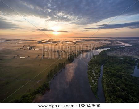aerial view of river at sunrise, fly over morning mist on the river.