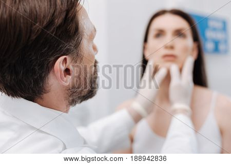 Consulting the patient. Neat careful competent doctor figuring out the areas he needing correcting for his client looking perfect