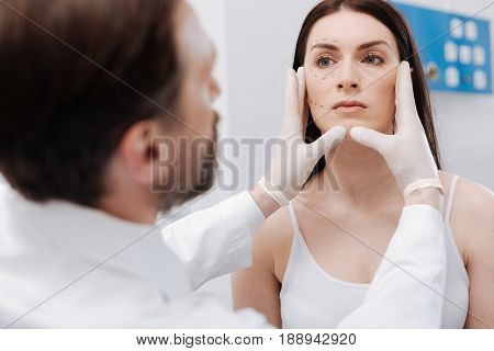 Expert on female looks. Distinguished dedicated mindful doctor examining patients face and telling her which procedures can be employing for improvement of her look
