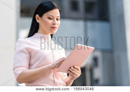 Asian woman expressing seriousness while looking at electronic tablet. She situating on street. Gadget concept