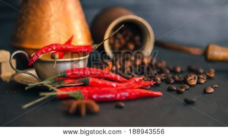 Coffee beans scattering off copper coffee pot and red hot chili peppers on black slate surface