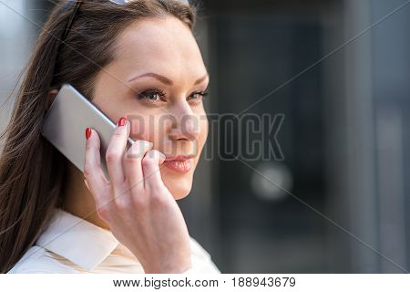 Portrait of female expressing thoughtfulness while telling by phone