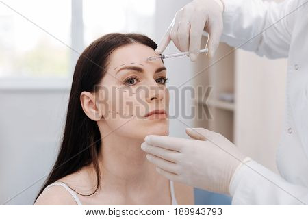 Risky step. Amazing charismatic elegant woman sitting at doctors office while he injecting her skin with botox for improving her features