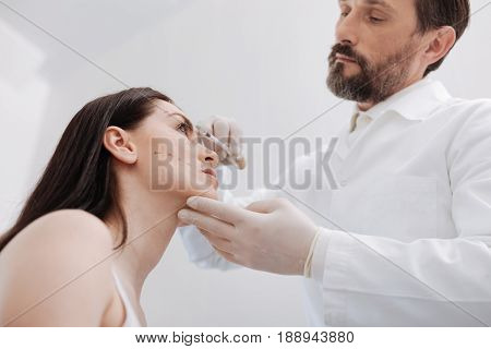 Hitting exact spots. Scrupulous motivated focused doctor estimating the precise dosage of the product for improving the look of his patient and not spoiling it