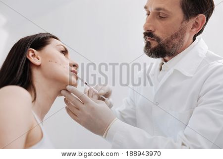 Fullness and beauty. Neat competent trained doctor assisting his patient in her desire of fuller lips by injecting them with special filler