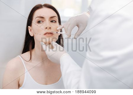 Sensual look. Stunning patient beautiful lady visiting a specialist and undergoing cosmetic procedure while trying altering her look
