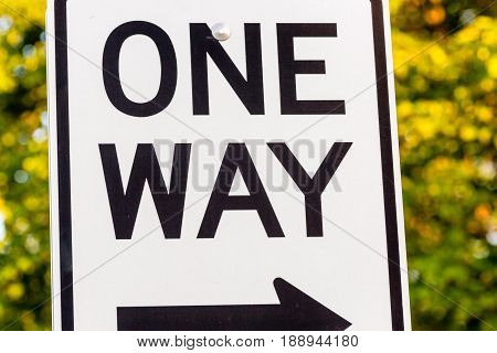 a close up of a one way sign