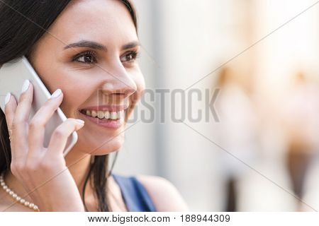 Close up face of businesswoman expressing cheerfulness while speaking by mobile. Portrait. Copy space