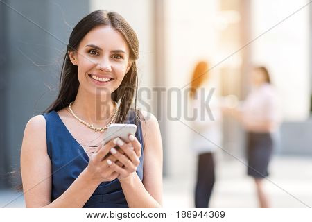 Portrait of lady demonstrating happiness while writing message by phone. She looking at camera