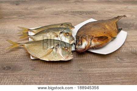 Smoked and dried fish closeup on wooden background. Horizontal photo.