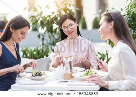 Cheerful asian female speaking with outgoing caucasian comrades while sitting at table in restaurant