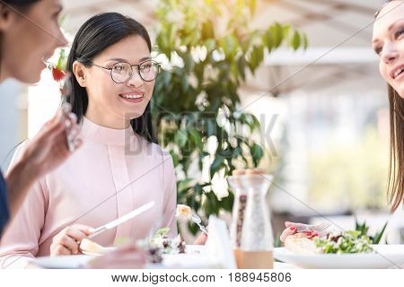 Asian female expressing happiness while speaking with affiliates in cafe. She eating food at table