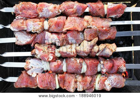 Raw red meat on barbecue close-up as gastronomic background for showcase of meat shop, restaurant or cafe